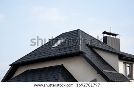 Black metal tile roof. Roof metal sheets. Modern types of roofing materials. Roof of the house, metal roof tile against the blue sky. Building.