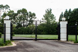 Black metal wrought iron driveway property entrance gates set in brick