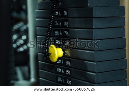 Black metallic or iron heavy plates stacked for sport, exercise, weight machine with kilogram and pound numbers in fitness gym on blurred grey background