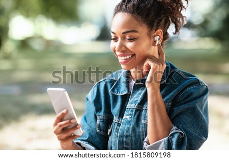 Black Millennial Girl Using Phone And Earbuds Making Video Call Siitting In Park Outside. Modern Communication Stock photo ©