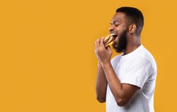 Black Millennial Guy Biting Burger Eating Junk Food Over Yellow Studio Background. Side View, Blank Space. African American Man Enjoying Tasty Cheeseburger. Overeating, Unhealthy Nutrition Habit