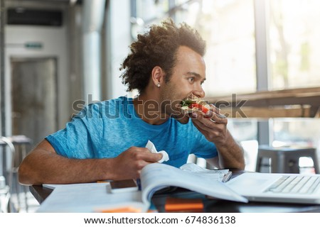 Black mixed race male student being busy with studying resting for minute eatting sandwich. Hungry student with dark skin working with books and laptop computer having lunch busy doing home assignment