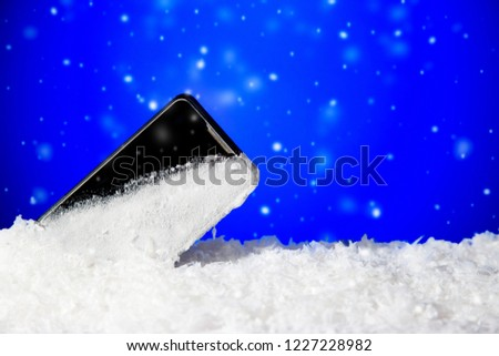Black mobile phone frozen in the ice on blue background with falling snowflakes with copy space. Winter background #1227228982