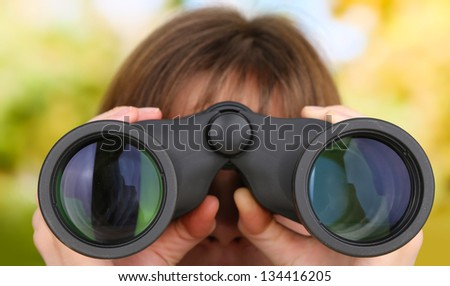 Black modern binoculars in hands on green background
