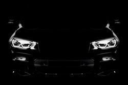 Black modern car headlights - front view. Silhouette of black sports car with headlights on black background.