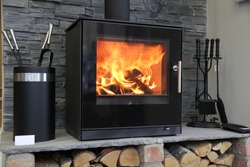 Black modern looking wood burning stove with logs underneath