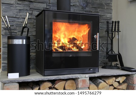Black modern looking wood burning stove with logs underneath  Stock fotó ©
