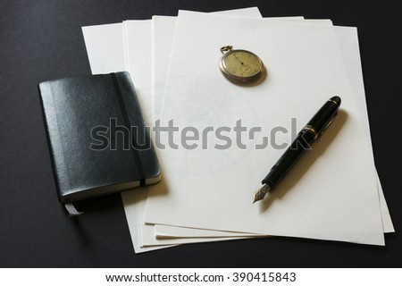 Black moleskin, white papers, fountain pen and pocket watch