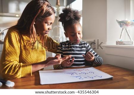 Black mom and child doing homework at kitchen