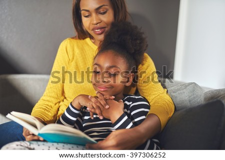 Black mom and daughter reading a book sitting on sofa smiling