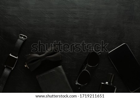 Black monochromatic composition on black background: watch, phone, sunglasses, purse, perfume, male butterfly. Minimalist black. Mens accessories. Copy space. Foto stock ©
