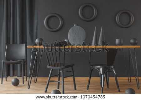 Black, monochromatic dining room interior with wooden table standing against a wall with rings decoration #1070454785