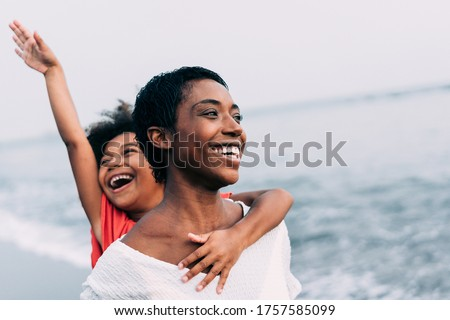 Black mother and daughter running on the beach at sunset time during summer vacation - Family people having fun together outdoor - Travel and happiness lifestyle - Focus on mom's face