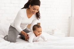 Black Mother Playing With Baby Toddler Crawling On Bed Indoor