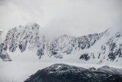 Black mountains with white snow on tops and glacier. Dramatic landscape with snowy mountains under cloudy gray sky in grayscale. Atmospheric alpine scenery with snow rocky mountains among low clouds.