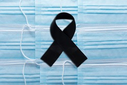 Black mourning tape on medical masks. Symbol of mourning and death of mourning for those killed by the coronavirus Covid-19. Mourning Background