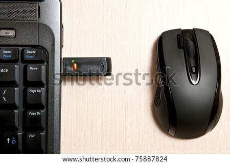 Black mouse and notebook on desk
