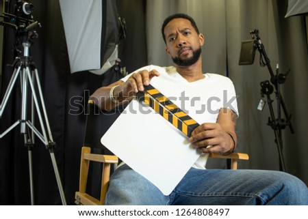 Black movie director sitting in a director's chair #1264808497