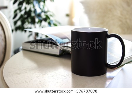Black mug, cup on a table with book, Mockup