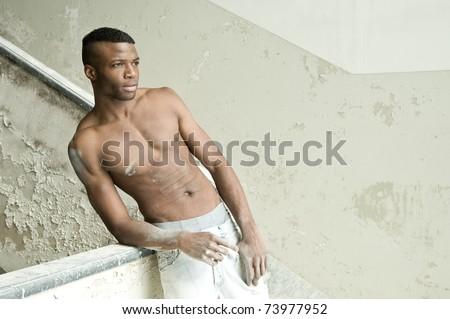 Black muscular man intense portrait, indoor. Inside abandoned building.