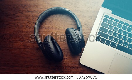 Black music headphone with laptop computer on wooden table. Top view with vintage filter. #537269095
