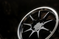 black new alloy wheels with a polished rim on a dark background close up