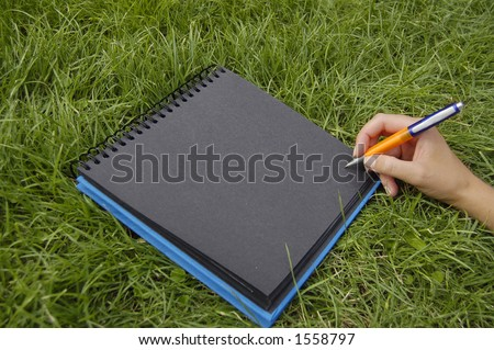black notebook in grass writing