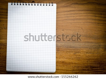 Black notebook on a wood background