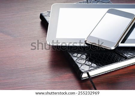 black notebook, tablet and on phone - Shutterstock ID 255232969