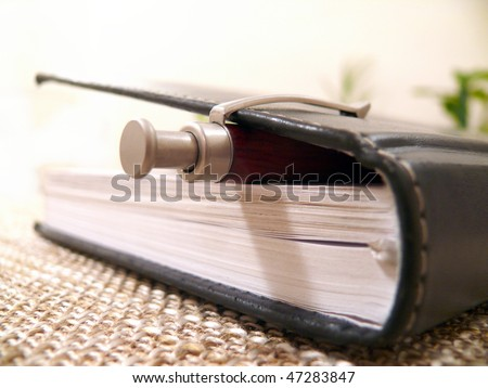 black notebook with a pen