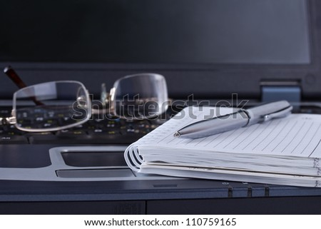 Black notebook with notepad pen and glasses lying on it