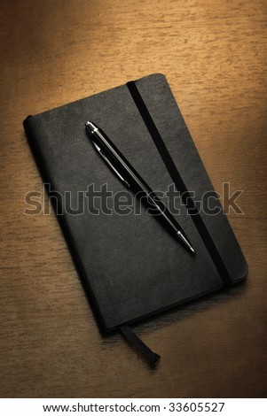 Black notepad and pen on table