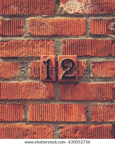 Black number 12 house number set against a terracotta brick wall. #630052736