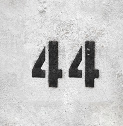 Black Number 44 on the white wall . Spray paint.