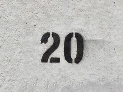 Black Number 20 on the white wall . Spray paint.