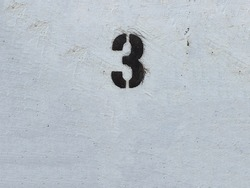 Black Number 3 on the white wall . Spray paint.