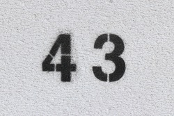 Black Number 43 on the white wall . Spray paint.