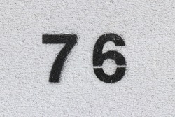 Black Number 76  on the white wall. Spray paint.
