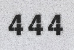 Black Number 444 on the white wall. Spray paint.