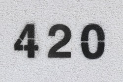 Black Number 420 on the white wall. Spray paint.