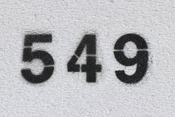 Black Number 549 on the white wall. Spray paint.