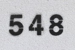 Black Number 548 on the white wall. Spray paint.