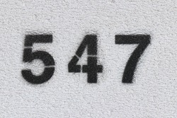 Black Number 547 on the white wall. Spray paint.