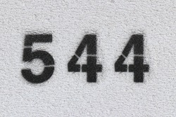 Black Number 544 on the white wall. Spray paint.