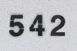 Black Number 542 on the white wall. Spray paint.