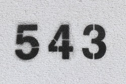Black Number 543 on the white wall. Spray paint.