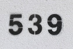 Black Number 539 on the white wall. Spray paint.