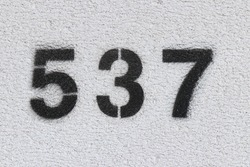 Black Number 537 on the white wall. Spray paint.