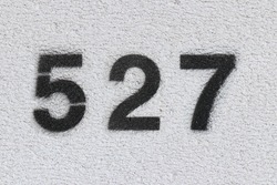 Black Number 527 on the white wall. Spray paint.