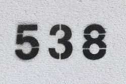 Black Number 538 on the white wall. Spray paint.